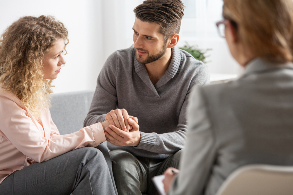 Young husband apologizing his worried wife during marital therapy with counselor